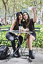 Two twin sisters taking a selfie at table in a park - GIOF02211