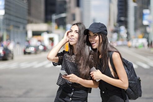 USA, New York City, two happy twin sisters with cell phones in Manhattan - GIOF02220