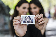 Two twin sisters holding an instant photo of themselves - GIOF02229