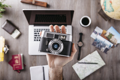 Overhead view of man's hand holding camera and travel items on table - JRFF01248