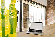 Laptop on table with businessman behind toned glass - KNSF01161