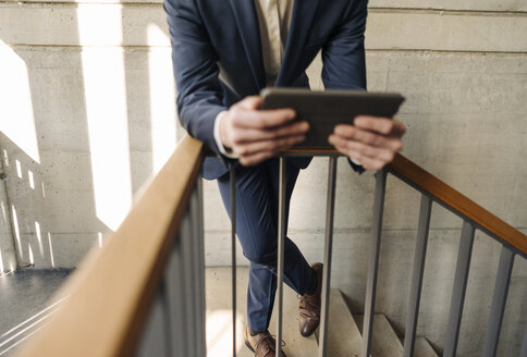 Businessman holding tablet in staircase - KNSF01170