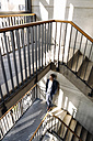 Businessman standing in staircase - KNSF01173