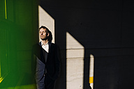 Businessman with closed eyes leaning against a concrete wall - KNSF01176