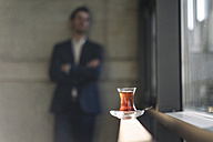 Glass of Turkish tea at the window with businessman in background - KNSF01179