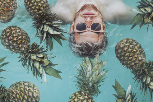 Young man in swiming pool surrounded by pineapples - RTBF00747