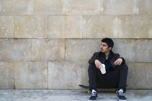 Young man sitting on skateboard holding disposable cup - KKAF00506