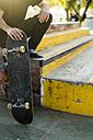 Man sitting with skateboard in a skatepark - KKAF00515