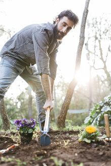 Man planting flowers in his garden - JRFF01274