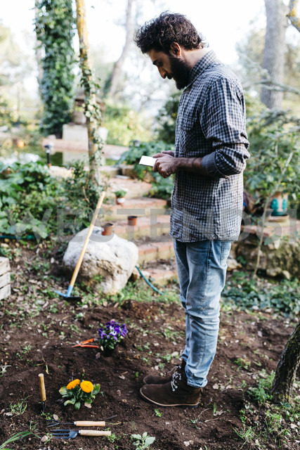Man taking photographs with a tablet of flowers planted in garden - JRFF01280