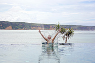 Indonesia, Lombok island, woman jumping into infinty pool - KNTF00757