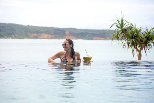 Indonesia, Lombok island, smiling woman in infinty pool - KNTF00760