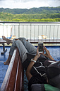 Indonesia, Lombok island, woman using cell phone on ship deck - KNTF00769