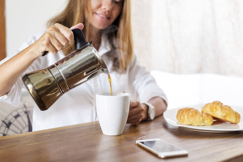 Woman at breakfast table pouring coffee into cup - KNTF00777