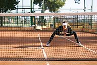 Teenage girl warming up on tennis court - VABF01261