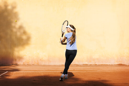 Teenage girl playing tennis on court - VABF01264
