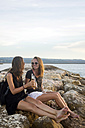 Indonesia, Bali, two women having a beer at the coast - KNTF00790