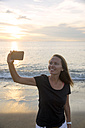 Indonesia, Bali, woman taking a selfie on the beach at sunset - KNTF00796