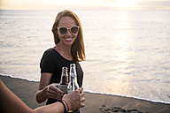 Indonesia, Bali, woman clinking beer bottle with friend on the beach at sunset - KNTF00799