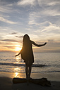 Indonesia, Bali, woman watching the sunset over the ocean balancing on a log - KNTF00802