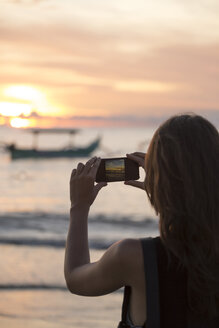 Indonesia, Bali, woman taking a picture of the sunset over the ocean - KNTF00805