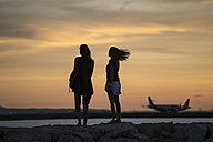 Indonesia, Bali, two women watching the sunset over the ocean - KNTF00808