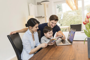 Family with laptop and guidebook planning vacation at home - SHKF00722