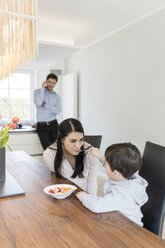 Mother and son having breakfast with father on the phone in background - SHKF00728