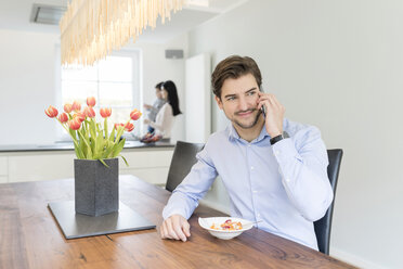 Man on the phone with mother and son in background - SHKF00731