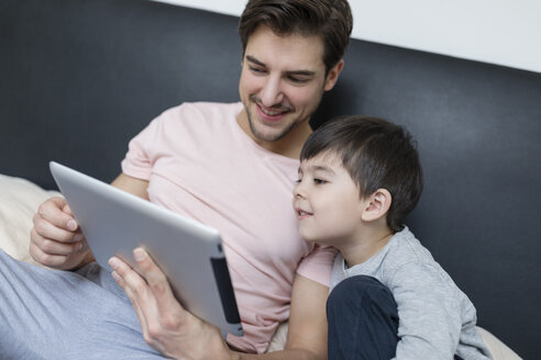 Father and son looking at tablet in bed - SHKF00740