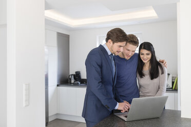 Consultant with laptop talking to couple at home - SHKF00749