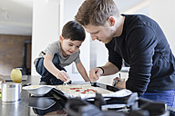 Father and son preparing pizza in kitchen together - SHKF00752