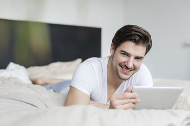 Portrait of smiling man lying on bed using tablet - SHKF00755