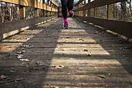 Close-up of woman running on a wooden bridge - SIPF01443