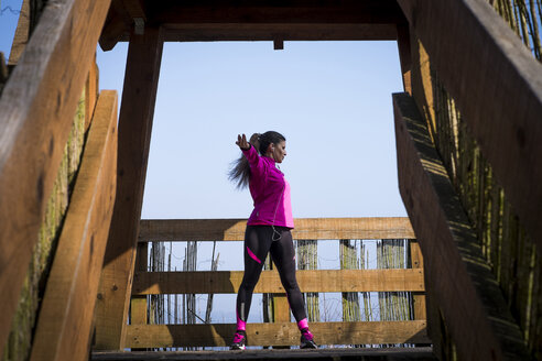 Woman stretching on wooden bridge - SIPF01446