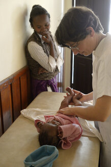 Madagascar, Fianarantsoa, Doctor examining baby for a mother and child group - FLK00796