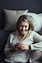 Smiling blond woman with glass of coffee relaxing on couch at home - NAF00062