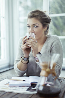 Portrait of young woman with glass of coffee looking through window - NAF00080