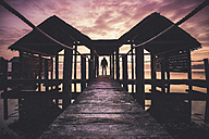 Italy, man standing on a pier at sunset - SIPF01456