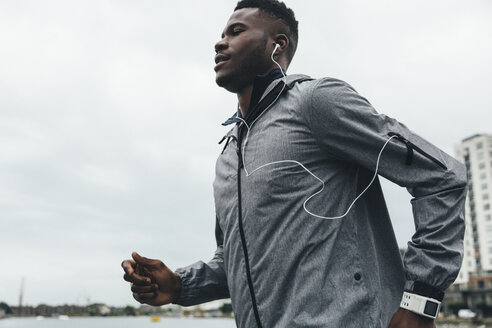 Young man running with earbuds and smartwatch - BOYF00668