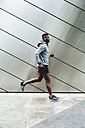 Young man running along building front - BOYF00671