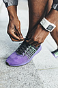 Close-up of athlete wearing smartwatch tying shoes - BOYF00683