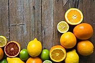 Sliced and whole lemons, oranges and limes on wood - GIOF02238