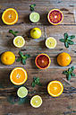 Sliced and whole lemons, oranges and limes and mint leaves on wood - GIOF02241