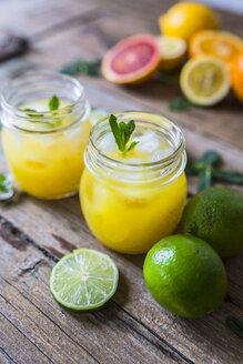 Glass of orange juice, limes, lemon and ice cubes - GIOF02247