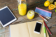 Glass of orange juice, notepad, pencils, tablet and cell phone - GIOF02253