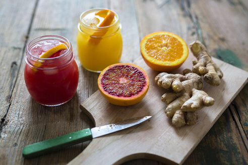 Two glasses of different orange juices, halves of oranges and ginger - GIOF02259