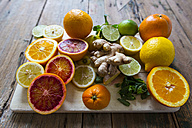 Sliced and whole lemons, oranges and limes, ginger root and mint leaves on wooden board - GIOF02265