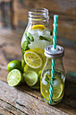 Glass bottles of infused water with lemon, lime, mint leaves and ice cubes - GIOF02268