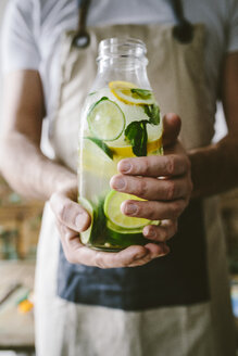 Man's hands holding glass bottle of infused water with lemon, lime, mint leaves and ice cubes - GIOF02271